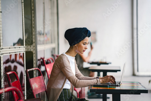 Fotomural  Portrait of a slim, young Muslim Malay woman sitting and working at a cafe during the day