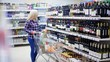 woman chooses wine in a supermarket