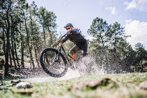 Male cyclist splashing water with mountain bike