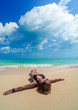 Woman laying on the white sand on a tropical beach with blue water ocean.