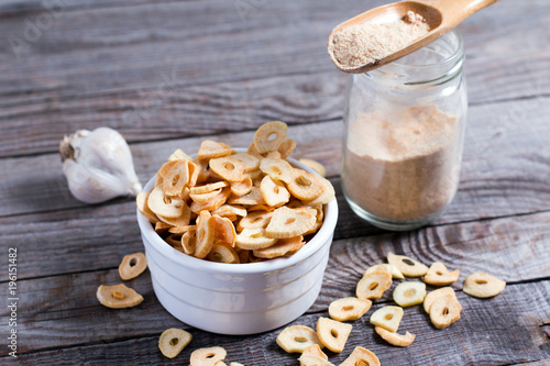 Fotografía  Spoon with granulated dried garlic on wooden background