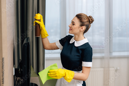 Photo young beautiful maid in uniform doing cleaning with rag and aerosol furniture cl