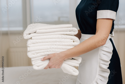 Fotografie, Obraz cropped shot of maid in uniform holding stack of clean towels in hotel suite