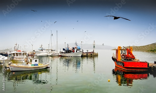 Fishing boats with reflections in an greek small quiet  harbor named Pachi at Winter