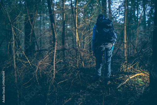 backpacker hiking in dark winter forest at dusk rear view buy