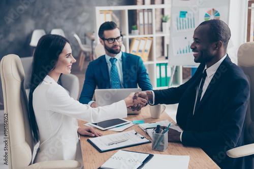 Fotografía  Partners making deal, shaking their hands, sitting in work place, wearing elegan