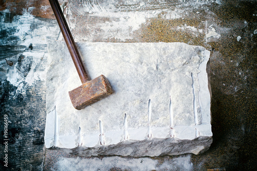 Fotografía  Closeup of a large piece of marble and a hammer after splitting.