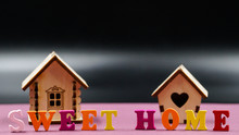 """The Phrase """"Sweet Home"""" Laid Out On A Pink Background With Two Toy Wooden Houses."""