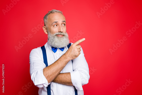 Fototapeta Portrait with copy space of minded, ponder, professional, retro stylist, barber with blue bowtie and suspenders pointing on empty place, product with forefinger, isolated on red background obraz