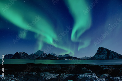 Foto auf Leinwand Nordlicht Northern Lights, Aurora Borealis shining green in night starry sky at winter Lofoten Islands, Norway