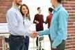 Businesspeople shaking hands before meeting In boardroom.
