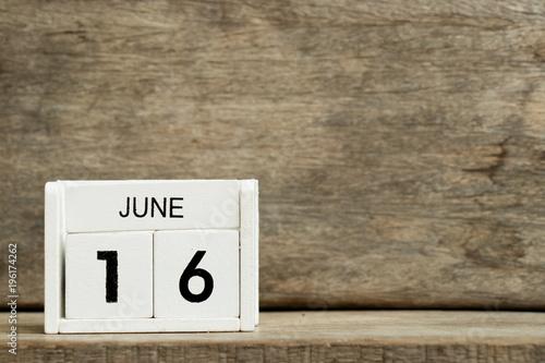 Vászonkép  White block calendar present date 16 and month June on wood background