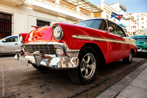 Valokuva  Cuba, Havana: American classic car with cuba flag parked on the street