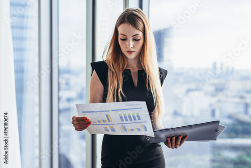 Female financial analyst holding papers studying documents standing against wind Canvas Print