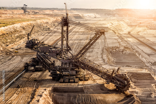 Fototapeta Bucket-wheel excavator mining in a open pit brown coal mine.