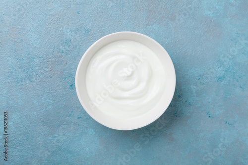 Greek yogurt in bowl on blue stone table top view.