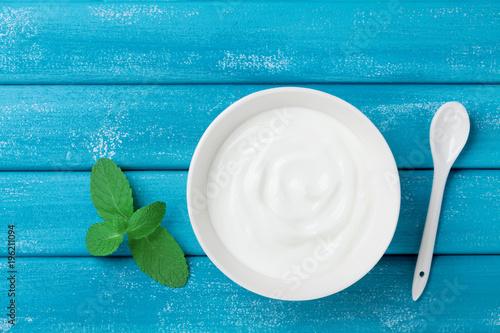 Fresh greek yogurt in bowl on blue vintage table top view.