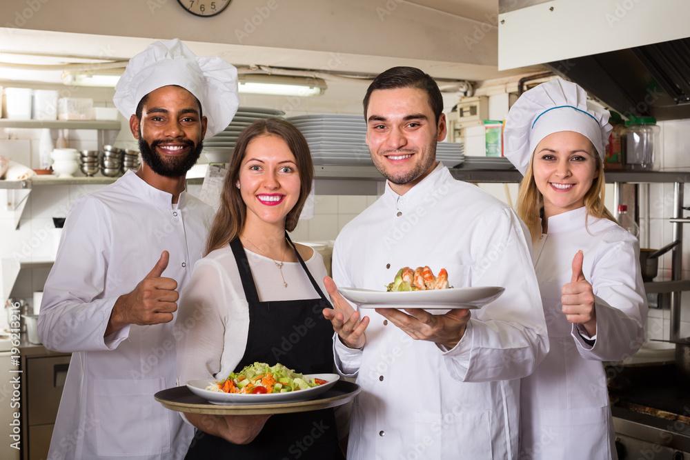 Fototapeta waitress and cooking team at kitchen