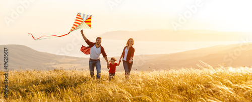 Fototapeta Happy family father,  mother and child daughter launch a kite on nature at sunset obraz