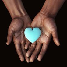 African Hands Holding A Blue Heart