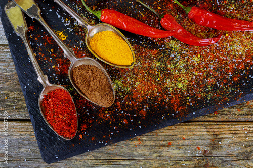 Fotografie, Obraz  Overhead view depicting cooking with spices in a rustic kitchen with bowls of co