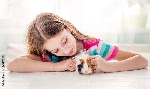 Fotografía  Girl stroking fluffy guinea pig