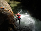 Canyoning - the young courageous girl abseiling into the canyon