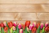 Fototapeta Tulipany - Spring easter tulips in bucket on wooden vintage background.