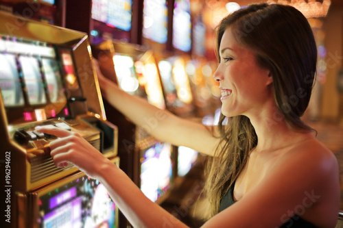 Fotografering Asian woman gambling in casino playing on slot machines spending money