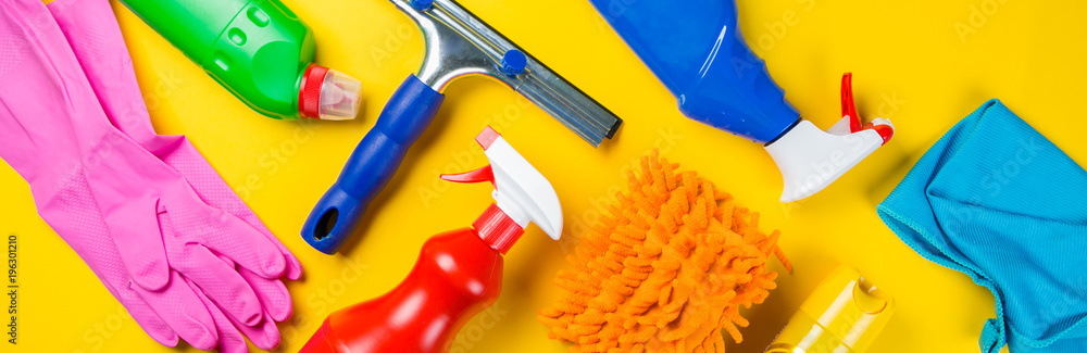 Fototapeta Cleaning concept - cleaning supplies on wood background