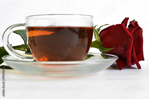 Staande foto Thee hot black tea in transparent glass cup on dish and red rose on white background