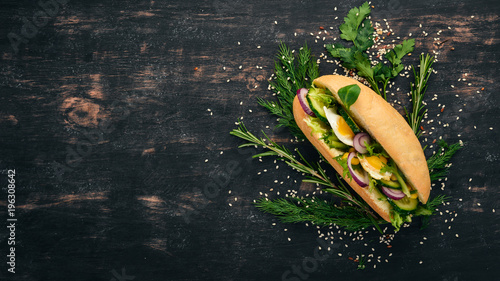 Poster Snack Burger, sandwich with quail egg, cucumber and corn. On a wooden background. Top view. Copy space.