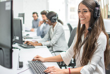 Young Smiling Operator Woman Agent With Headsets Working In A Call Centre.