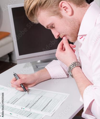 Obraz na plátně Junger Mann sitzt am Schreibtisch und arbeitet an Steuerformularen