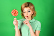 canvas print picture - Pin up girl. Beautiful woman with glamour bright makeup holding lollipop. Isolated on green background. Girl tell secret.