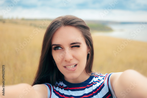 Fotomural  Clumsy Girl Trying to Take a Selfie in Nature