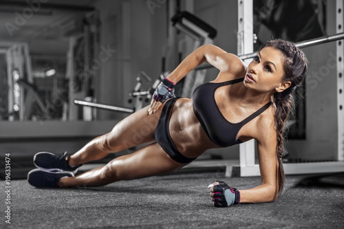 Attractive young woman is doing plank exercise while working out in gym