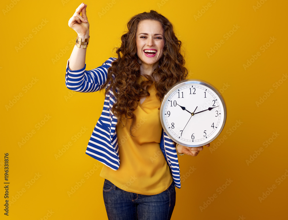 Fototapety, obrazy: happy woman on yellow background with clock snapping fingers
