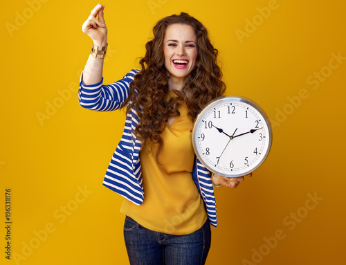 Fototapeta happy woman on yellow background with clock snapping fingers obraz
