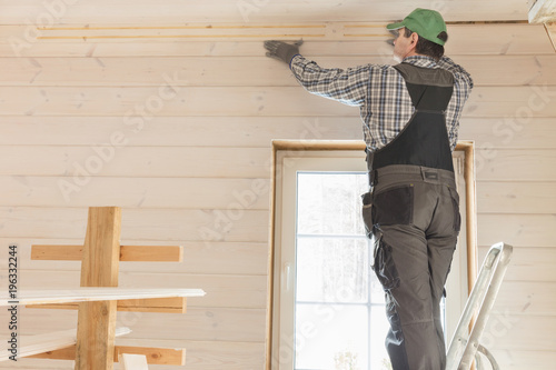 Construction worker thermally insulating eco wooden frame house with ...