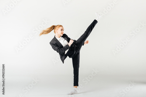 businesswoman performing kick in suit isolated on grey Wallpaper Mural