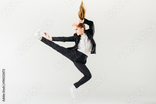 Photo  female karate fighter jumping and performing kick in suit isolated on grey