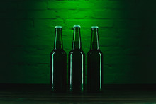 Close-up View Of Green Bottles Of Beer Near Green Brick Wall