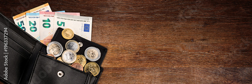 Fototapeta euro coin and bank note in black  leather wallet on wide wood wooden panorama business finance background with copy space  obraz