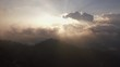 aerial shot sunrise over the mountain behind rain cloudy sky camera moving left to right