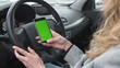 Woman sits in the modern car and using smartphone - closeup hands. Green screen.Chroma key