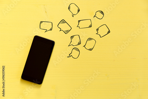 Valokuva  Smartphone on yellow background with text bubbles around
