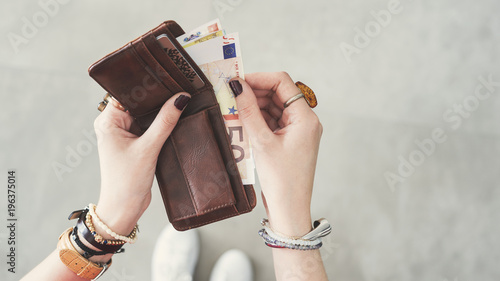 Woman taking out  euro money from her pocket wallet top view