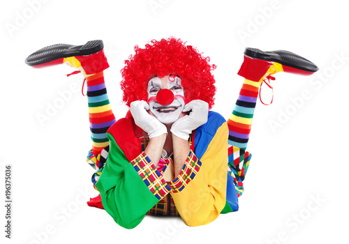 Happy clown  laying on the floor isolated over white background