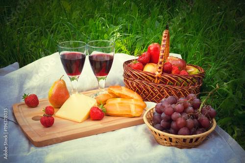 Zdjęcie XXL Ustawienie piknik na zewnątrz z dwoma kieliszkami czerwonego wina, sera i dojrzałych owoców na serwetce